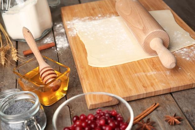 Surowe ciasto francuskie z wałkiem do ciasta na drewnianej desce