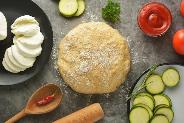 Surowe ciasto i świeże składniki na pizzę wegańską.