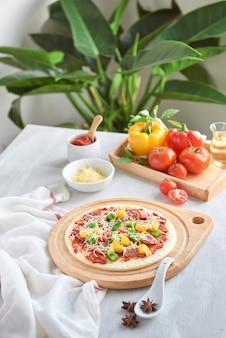 Surowe ciasto na pizzę z sosem pomidorowym i dodatkami