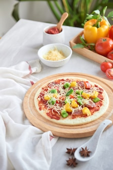 Surowe ciasto na pizzę z sosem pomidorowym i składnikami
