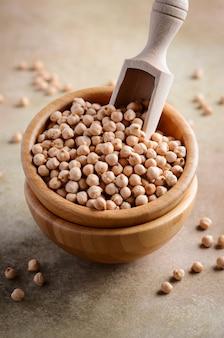 Surowe ciecierzycy organiczne w drewnianej misce, zdrowy wegański wegetariański składnik żywności.