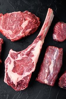 Surowe czerwone mięso wołowe marmurkowe z kością w zestawie, na czarnym kamiennym tle