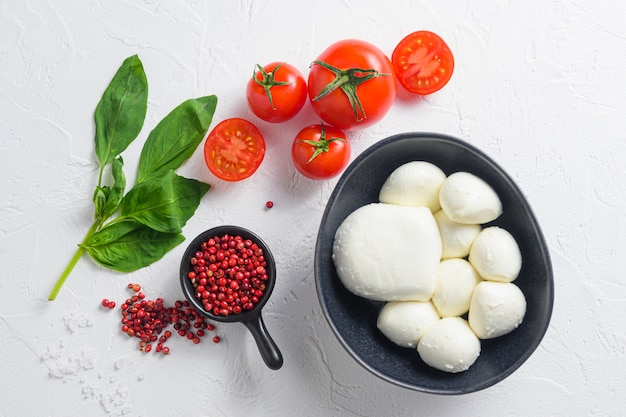 Surowe, dojrzałe kulki z sera mozzarella ze świeżymi liśćmi bazylii i pomidorkami cherry