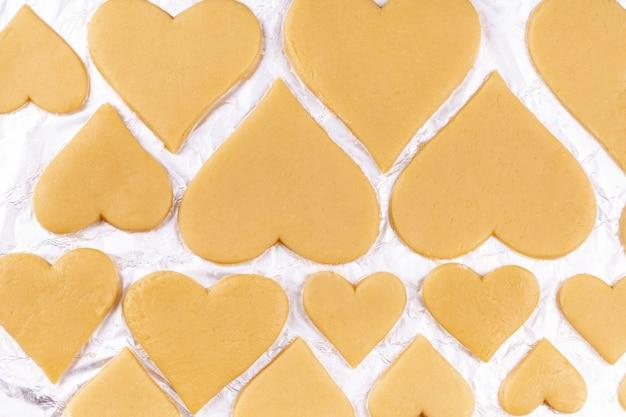 Surowe domowe ciasteczka w kształcie serca leżą na folii do pieczenia i przygotowują się do wysłania do piekarnika