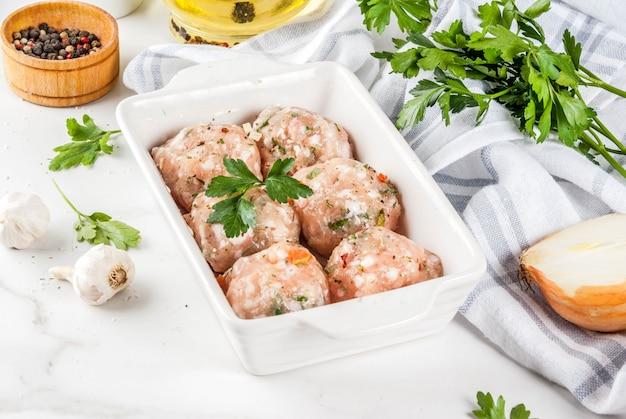 Surowe domowe klopsiki z kurczaka lub indyka w naczyniu do pieczenia