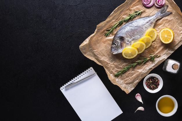 Surowe dorado na papierze do gotowania z przyprawami i zeszytem na przepis lub menu. zdrowa żywność, owoce morza. widok z góry na białym tle.