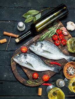 Surowe dorado z rybami morskimi z ziołami, przyprawami i butelką białego wina. na czarnym tle rustykalnym.