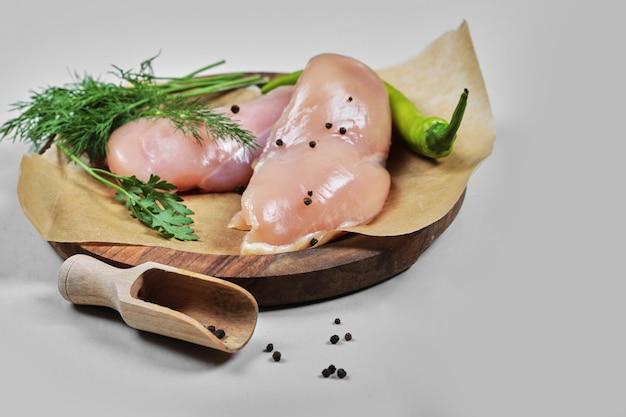 Surowe filety z kurczaka na drewnianym talerzu z łyżką