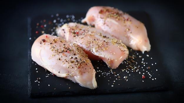 Surowe filety z kurczaka z przyprawami na kamiennej desce.