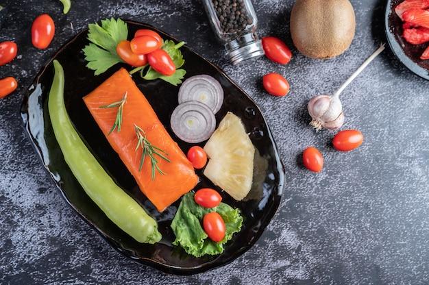 Surowe filety z łososia, pieprz, kiwi, ananasy i rozmaryn na talerzu i podłodze z czarnego cementu.