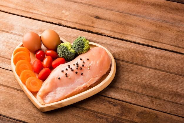 Surowe filety z piersi kurczaka bez kości z przyprawami, rozmarynem, marchewką i jajkiem na talerzu sercowym