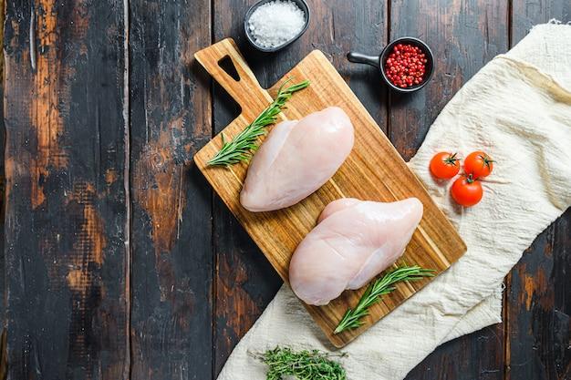 Surowe filety z piersi kurczaka i warzywa na desce do krojenia przesadne drewniane tło widok z góry miejsce na tekst.