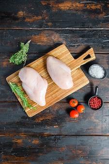 Surowe filety z piersi kurczaka i warzywa na desce do krojenia