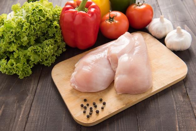 Surowe filety z piersi kurczaka i warzywa na drewnie