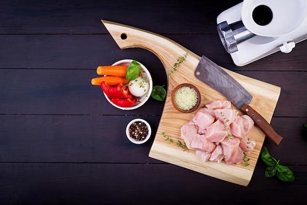 Surowe filety z piersi kurczaka na drewnianej desce do krojenia z ziołami i przyprawami. widok z góry