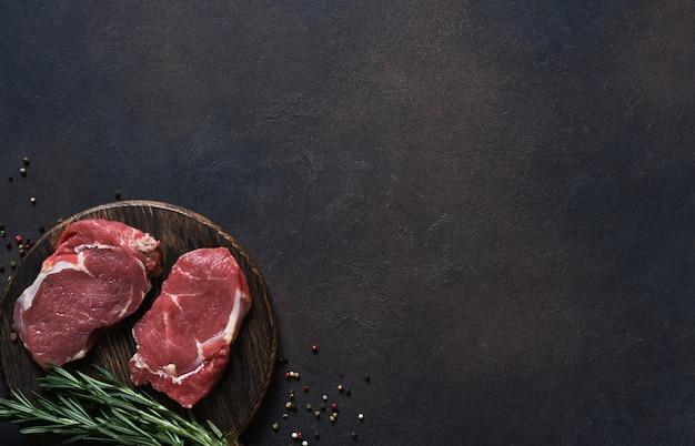 Surowe gotowanie stek wołowy ribeye z raspmarine na drewnianej desce. widok z góry z miejscem na kopię