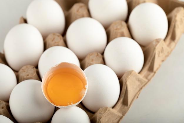 Surowe jaja kurze w pudełku na jajka na białej powierzchni.