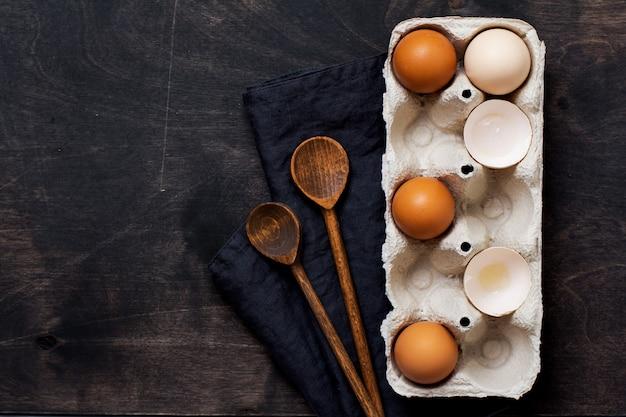 Surowe jaja kurze w pudełku z serwetką i drewnianymi łyżkami