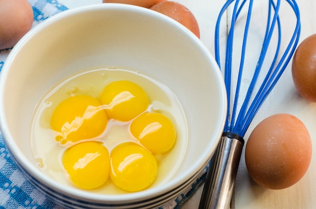 Surowe jajka i korona na białej powierzchni
