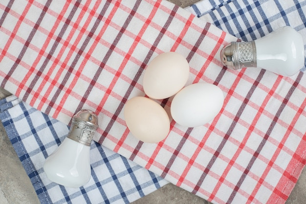 Surowe jajka i przyprawy z obrusem na marmurowej powierzchni. wysokiej jakości zdjęcie