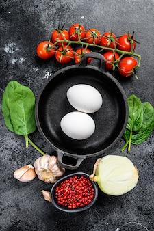 Surowe jajka na patelni w otoczeniu świeżych składników