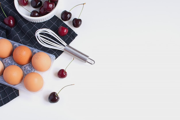 Surowe jajka trzepaczka forma do pieczenia i czarna serwetka w kratkę dojrzałe wiśnie