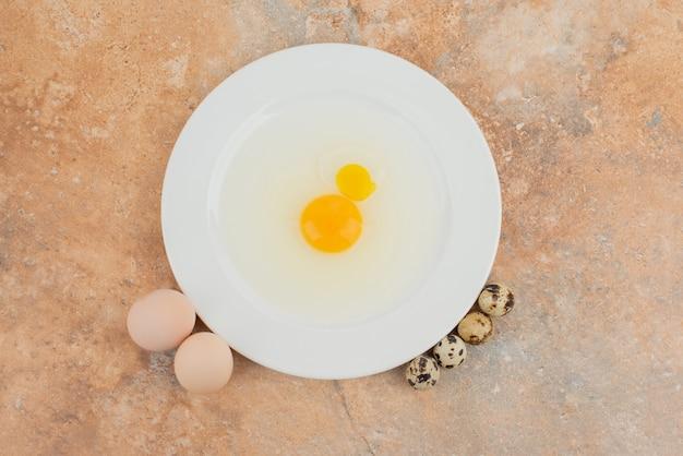 Surowe jajko na białym talerzu i kilka jaj przepiórczych.