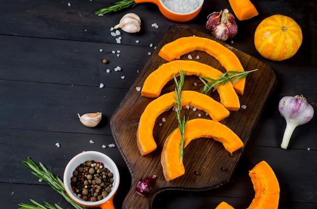 Surowe kawałki dyni na desce do krojenia z rozmarynem, solą, przyprawami na starym ciemnym stole. warzywa przygotowane do pieczenia w piekarniku. jesienna kuchnia domowa