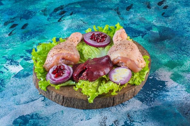 Surowe kawałki kurczaka z warzywami na desce
