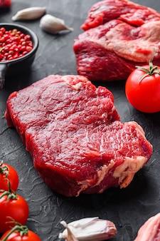 Surowe kawałki stek wołowy rumsztyk, z ziołami, przyprawy na czarnym stole, widok z boku.