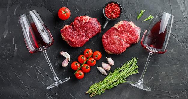 Surowe kawałki wołowiny z rampą z ziołami i kieliszkami do czerwonego wina