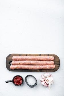 Surowe kiełbaski wołowe, leżak na płasko, na białym stole