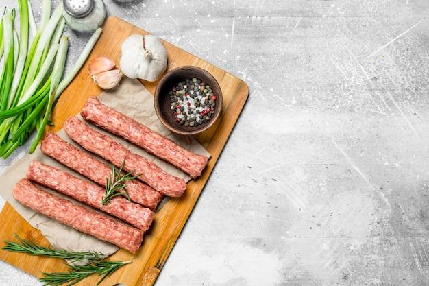 Surowe kiełbaski wołowe z czosnkiem i ziołami na rustykalnym stole.