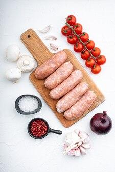 Surowe kiełbaski wołowe z pomidorami i cebulą, na białym stole