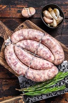 Surowe kiełbaski z mięsa wieprzowego i wołowego na drewnianej desce do krojenia