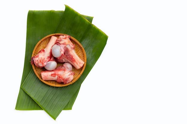 Surowe kości wieprzowe na liściach bananowca na białym tle.
