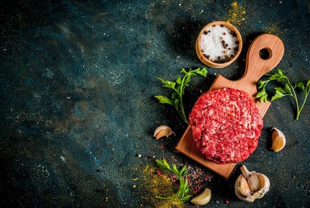 Surowe kotlety burgerowe z solą, pieprzem, olejem, ziołami i przyprawami