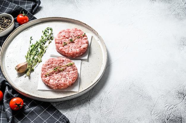Surowe kotlety drobiowe, paszteciki z mielonego mięsa. organiczne mielone mięso. widok z góry. skopiuj miejsce