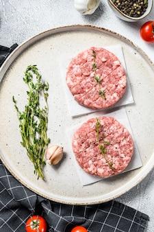 Surowe kotlety drobiowe, paszteciki z mielonego mięsa. organiczne mielone mięso. widok z góry