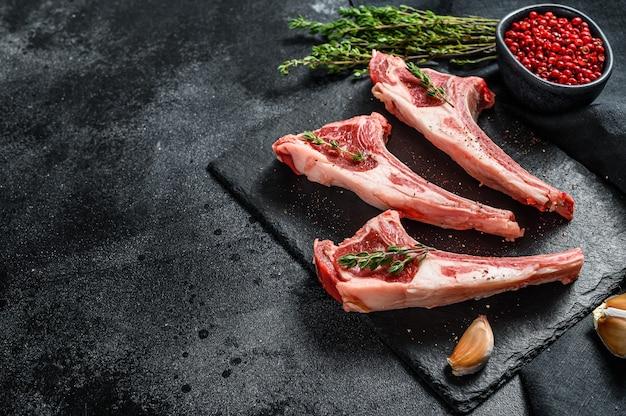 Surowe kotlety jagnięce, rack of lamb z rozmarynem i przyprawami. ekologiczny stek mięsny. czarne tło
