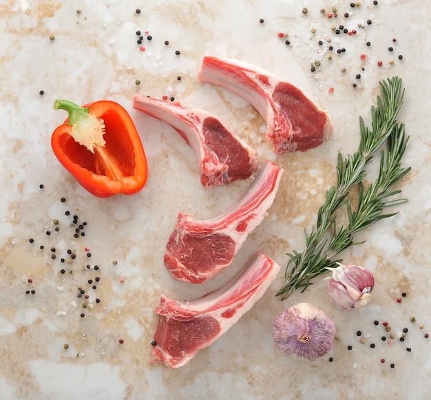 Surowe kotlety jagnięce z rozmarynem, czosnkiem i pieprzem
