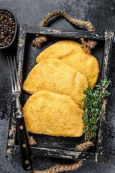 Surowe kotlety mięsne z kurczaka cordon bleu na drewnianej tacy z ziołami.