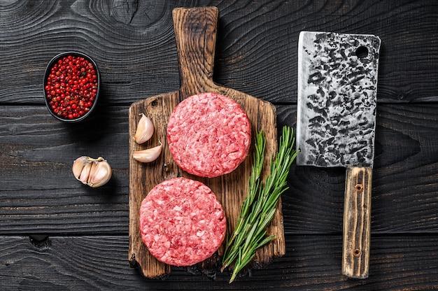 Surowe kotlety stekowe z mielonym mięsem wołowym i rozmarynem na drewnianej desce do krojenia z tasakiem do mięsa