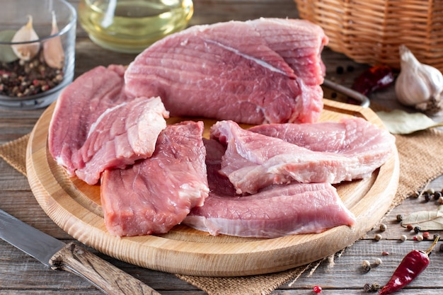 Surowe kotlety wieprzowe gotowe do gotowania na desce w rustykalnej kuchni. świeża wieprzowina.