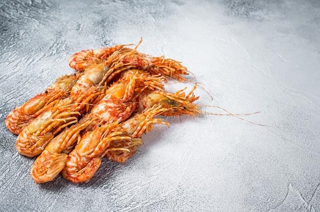 Surowe krewetki grenlandzkie na stole w kuchni. białe tło. widok z góry. skopiuj miejsce.