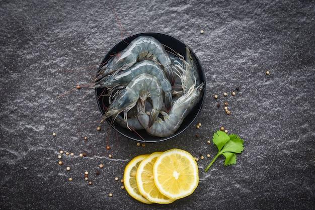 Surowe krewetki na misce / świeże krewetki krewetkowe do gotowania z przyprawami cytryny i selera na ciemnym tle