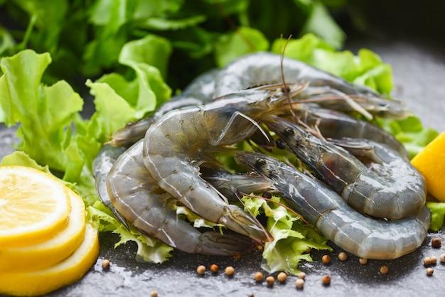 Surowe krewetki na talerzu, świeże krewetki krewetkowe nieprzygotowane z przyprawami sałata z cytryny i warzyw lub zielony dąb na ciemnym tle w restauracji z owocami morza