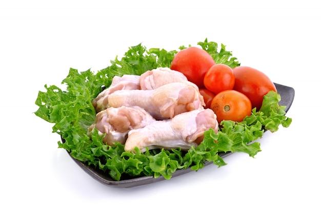 Surowe kurczak nogi, pomidory na talerzu odizolowywającym i