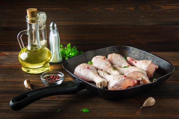 Surowe kurczak nogi w smaży niecce na drewnianym stole. składniki mięsa do gotowania.