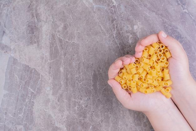 Surowe makarony w dłoni osoby